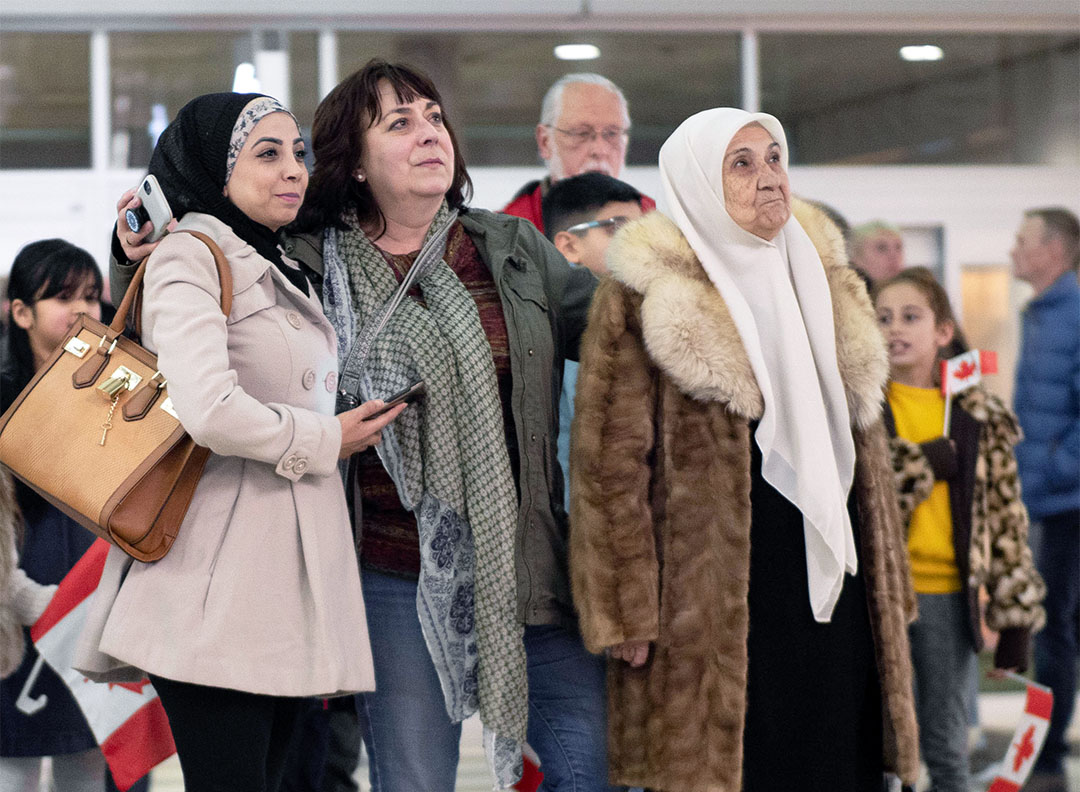 Fatema, Shelley and Abdulnaser's sister, Souhair stand together, looking toward the escalator at Regina International Airport.