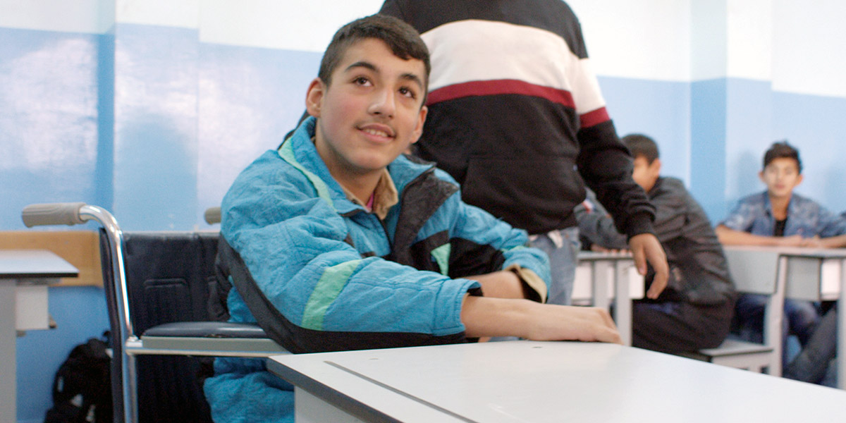 Abdulrahman, who uses a wheelchair, sits smiling at his desk.
