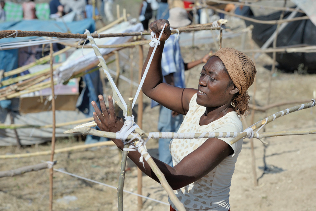 In Haiti, a woman ties binding around poles as she works on building a structure after an earthquake