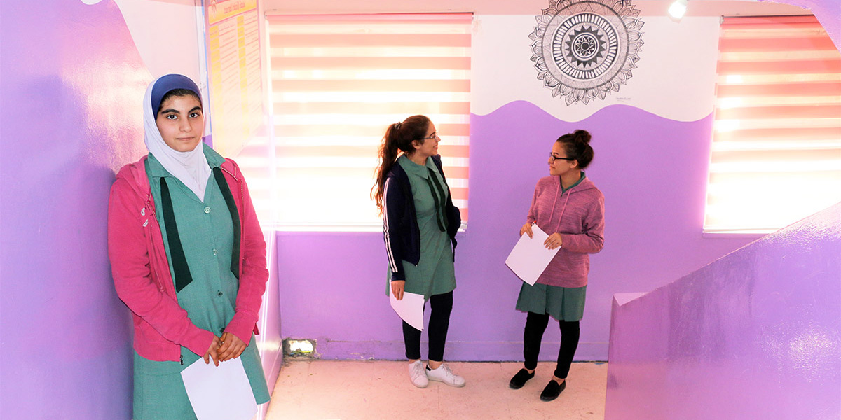 Students stand in a newly renovated, brightly painted hallway at Bint Adi Secondary School for Girls.