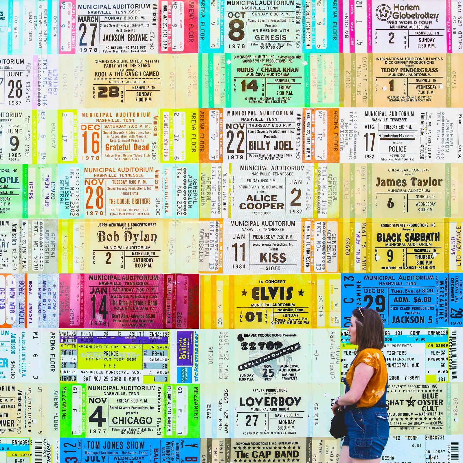 A woman walks past a wall of event ticket stubs