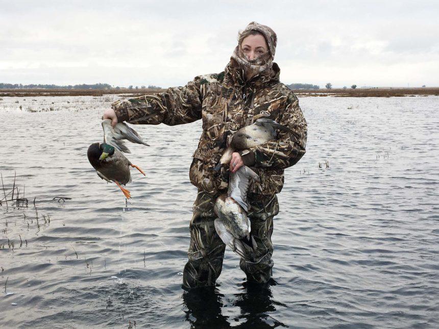 A hunter retrieves ducks