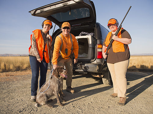 A group of women laugh before a pheasant hunt with California Waterfowl.