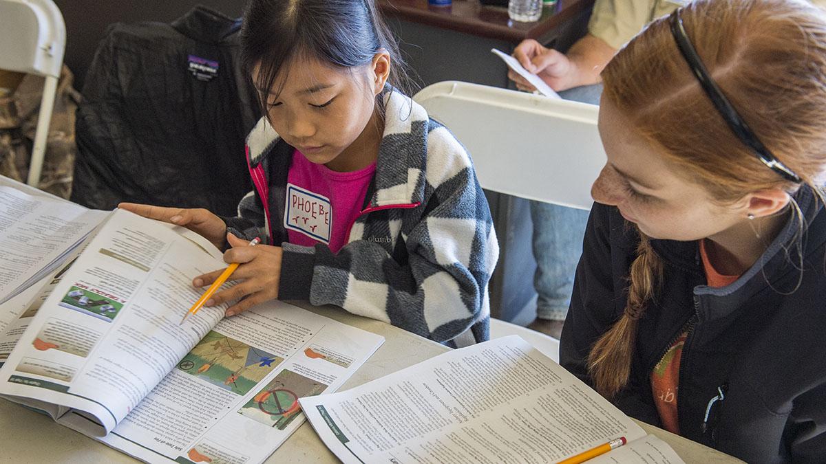 Aspiring hunters look through hunter education book