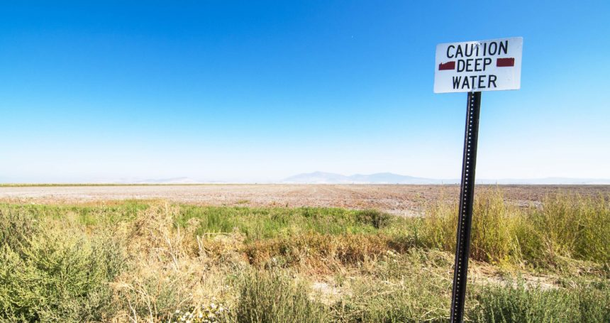 "Photo shows a bone-dry field at the Lower Klamath National Wildlife Refuge behind a sign that says, ""Caution, deep water"""
