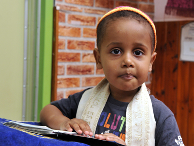 Young boy with kippah and siddur saying a prayer